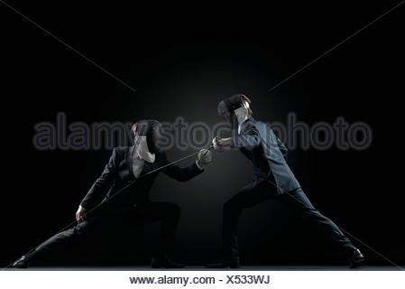 Businessmen fencing - Stock Photo