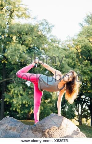 Woman in Ardha Chandra Chapasana pose - Stock Photo