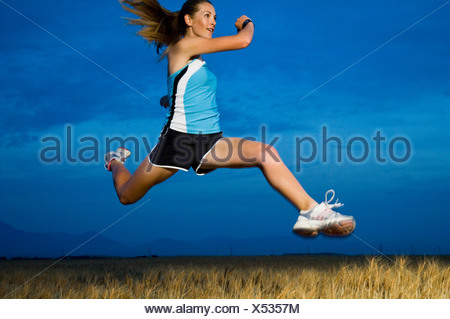 Woman in athletic gear jumping - Stock Photo