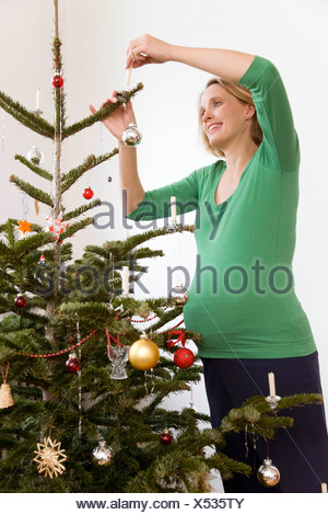 pregnant woman decorating christmas tree - Stock Photo
