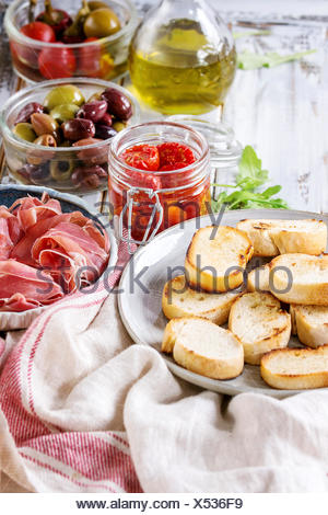 Ingredients for making tapas or bruschetta. Crusty bread, ham prosciutto, sun dried tomatoes, olive oil, olives, pepper, greens on plates over white p - Stock Photo
