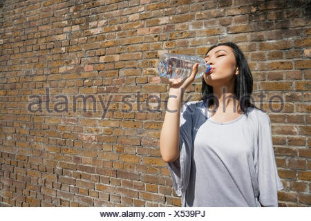 Beautiful young woman drinking water against brick wall - Stock Photo