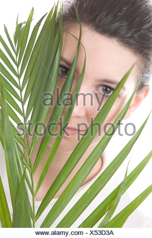 Face of a young woman hidden behind a leaf, Winnipeg, Manitoba - Stock Photo