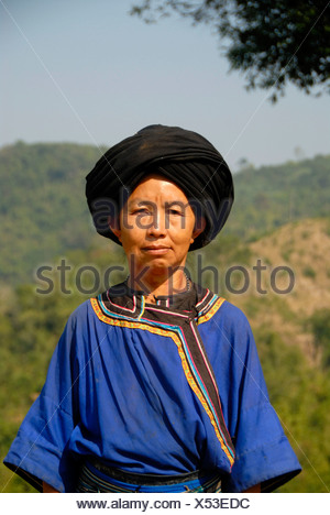Portrait of a woman of the Ho ethnic group in traditional colourful blue dress and black turban, Phongsali or Phongsaly District - Stock Photo