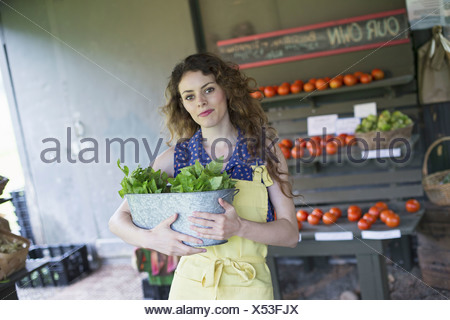 An organic farm stand. A woman sorting vegetables. - Stock Photo