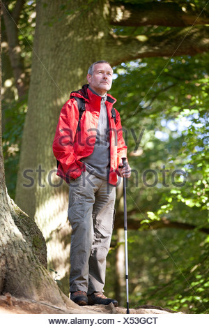 A mature man standing in the countryside looking at his surroundings - Stock Photo