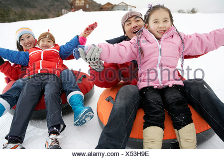 Parents And Children Riding On Inflatable Snow Tube - Stock Photo