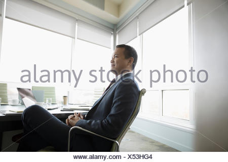 Attentive business people with hands clasped in meeting ...