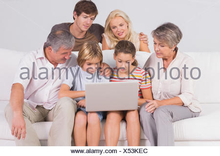 Family looking at laptop on couch - Stock Photo