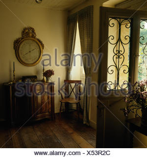 Large antique barometer above antique cupboard in traditional hall with wooden flooring and a half glazed door with a grille - Stock Photo
