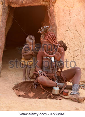 Himba woman with child in front of the mud hut, Kaokoveld, Namibia - Stock Photo