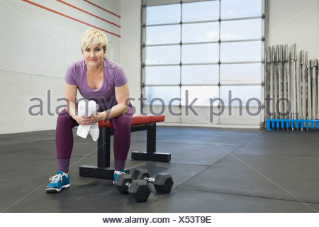 Portrait of woman sitting on bench in gym - Stock Photo