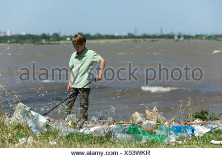 Boy picking up trash on polluted shore - Stock Photo