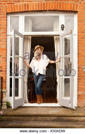 Mid adult woman looking out from patio doors - Stock Photo
