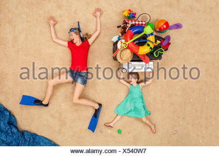 Mother and daughter running to the sea, carrying beach equipment on the head - Stock Photo