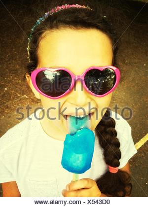 High Angle Portrait View Of Girl In Sunglasses Licking Blue Ice Candy - Stock Photo