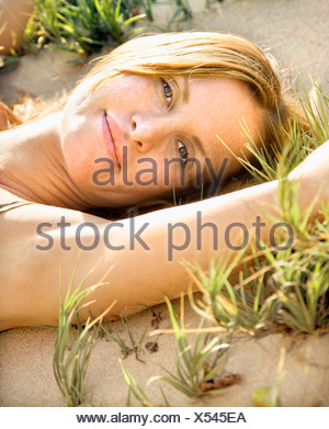 Close up portrait of attractive redheaded woman lying in grassy sand looking at viewer - Stock Photo
