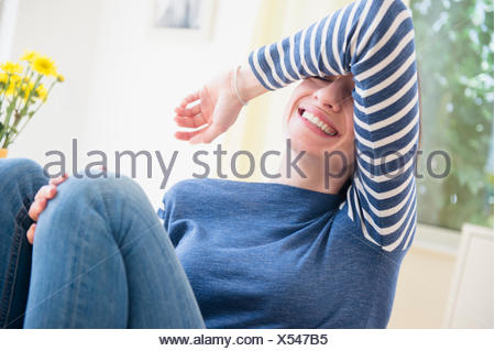Woman shielding her eyes and laughing - Stock Photo