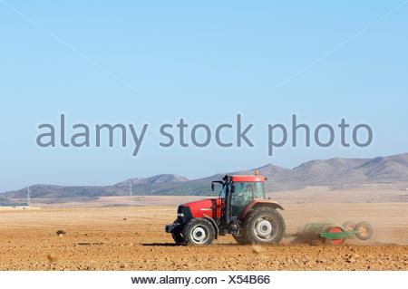 red tractor tilling a field of crops on a clear day in Belchite, Saragossa, Aragon, Spain - Stock Photo
