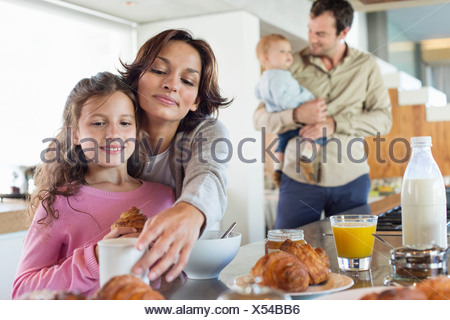 Girl having breakfast beside her mother at a kitchen counter - Stock Photo