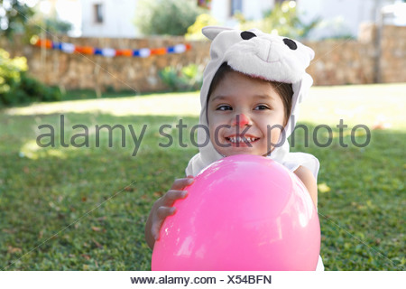 Young girl in rabbit costume with balloon - Stock Photo