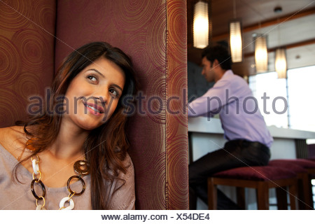 Woman in a restaurant smiling - Stock Photo
