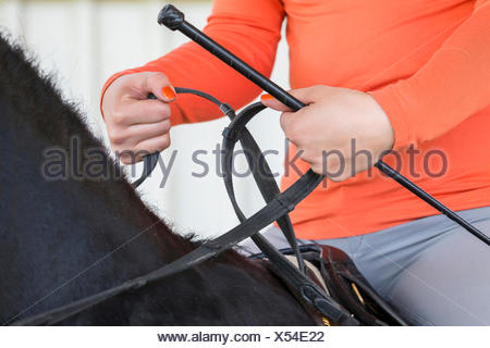 Manner holding the reins Turned-in wrist joint - Stock Photo