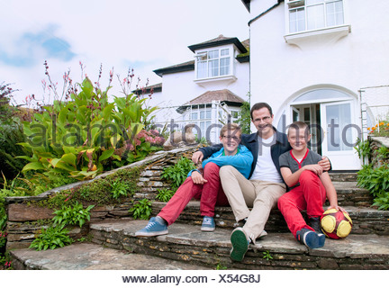 Father and sons sitting on steps in garden - Stock Photo