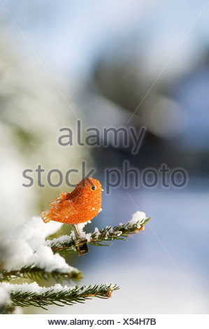 Bird-shaped figurine on fir branch, close-up - Stock Photo