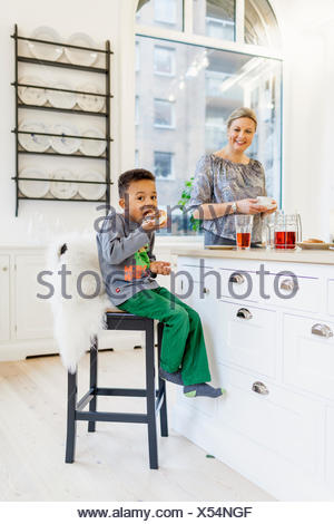 Happy mother watching son having breakfast in kitchen - Stock Photo
