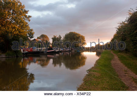 narrowboats and towpath along Cooks Wharf at sunset, Grand Union Canal Outer Aylesbury Ring, Cheddington, Buckinghamshire, England - Stock Photo