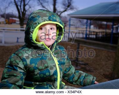 Boy Wearing Jacket In Playground - Stock Photo