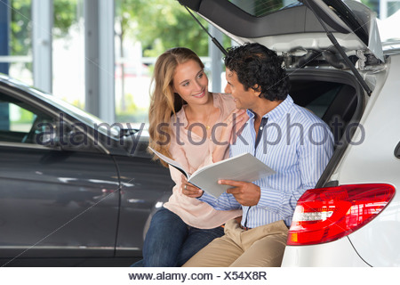 Couple looking at brochure in hatchback of car in car dealership showroom - Stock Photo