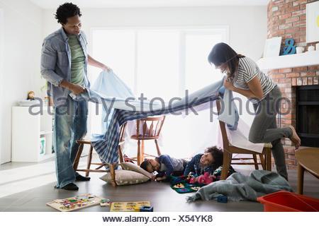 Parents creating fort over sleeping children - Stock Photo