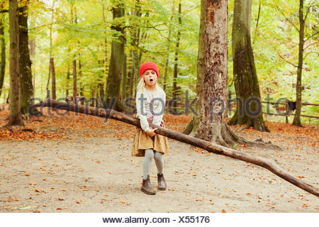 Girl carrying log while standing in forest - Stock Photo