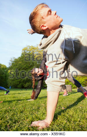 Young man and woman exercising in park - Stock Photo