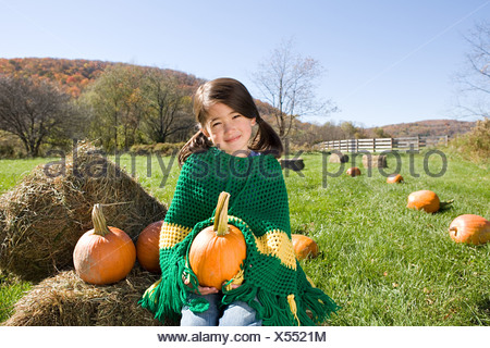 Girl in field with pumpkins - Stock Photo