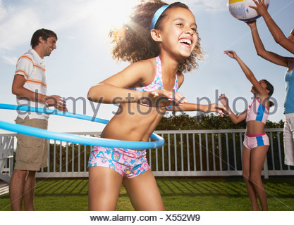 Girl in swimsuit with hula hoop and family playing in background - Stock Photo