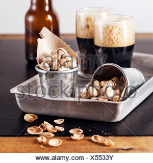 Dark beer and salted pistachios - Stock Photo
