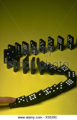 Cause effect action with dominoes chain reaction - Stock Photo