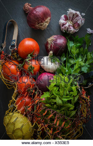 Vegetables in string bag fresh from the market on slate background: Top view - Stock Photo