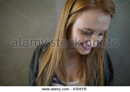 Portrait smiling young woman red hair looking down - Stock Photo