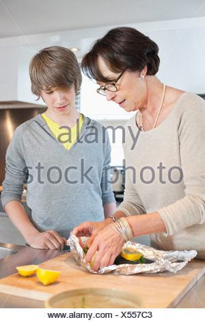 Elderly woman preparing seafood with her grandson in a kitchen - Stock Photo