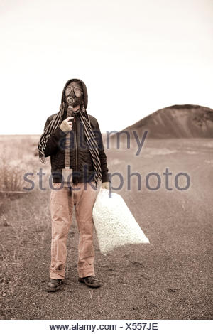 Portrait of a man wearing a gas mask standing in a desolate landscape. - Stock Photo