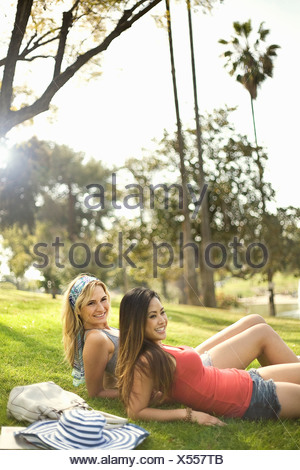 Two young women having fun and relaxing in park - Stock Photo