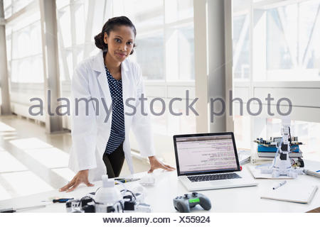 Portrait of confident engineer at desk with robots - Stock Photo