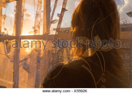 Mid adult woman, behind net curtain, looking out of window, rear view - Stock Photo