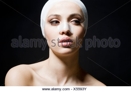 young woman with plaster on face - Stock Photo