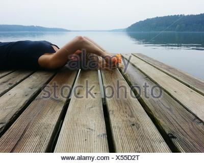 Woman Lying On Wooden Pier In Front Of River Against Sky - Stock Photo