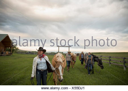 Female ranchers walking horses in rural pasture - Stock Photo